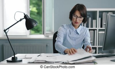 Disappointed woman in formal clothes and eyeglasses sitting at workplace and searching for something among stack of documents. Overwork and stress concept.