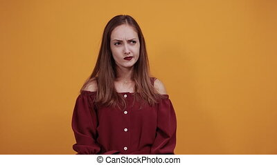 Disappointed woman in maroon dress isolated on orange background in studio keeping hands together, praying . People sincere emotions, lifestyle concept.