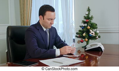 Disappointed young businessman counts money before Christmas