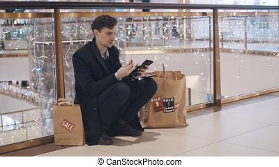 Disappointed young man sitting on the floor in mall without money after Black Friday sales