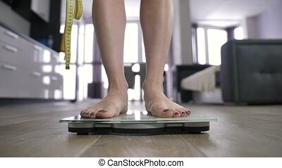 Disappointing weight results on bathroom scale - Young woman...