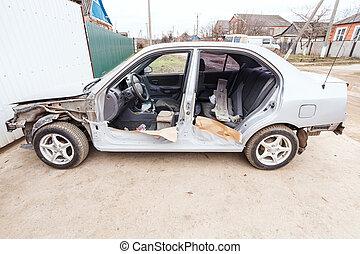 disassembled car near the garage door