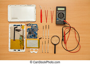 Disassembled tablet and tools on a wooden background. View from above.