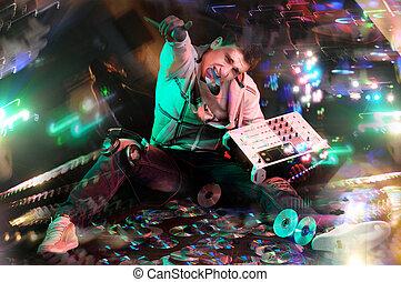 Disc Jockey - Disc jockey sitting on CDs with electronic ...