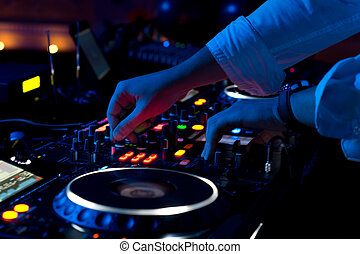 Disc jockey mixing music - Close up view of the hands of a...