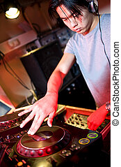 Disc Jockey - Disc jockey at work behind a turn table in a...