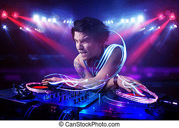 Disc jockey playing music with light beam effects on stage...