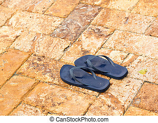 Discarded childs blue flip flops on paved deck by swimming pool with water in indentations