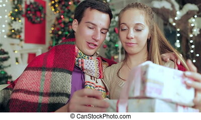 Disclose Christmas gifts - Loving couple dressed in sweater...