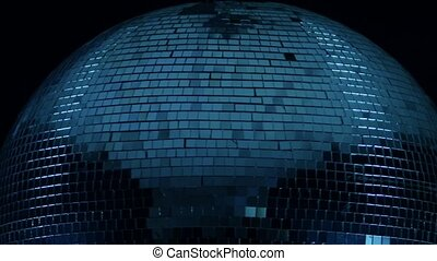 Disco ball close-up in the center of a spin on a black...