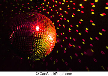 Disco ball red - yellow with reflections on the wall