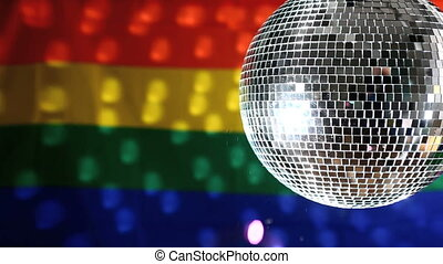 Disco ball revolving against gay pride flag with bubbles...