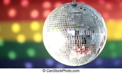 Disco ball spinning against rainbow