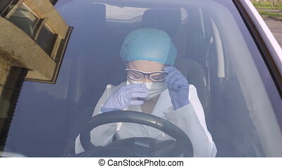 Disconsolately doctor in car during coronavirus pneumonia sickness. Professionals going to emergency call-out. Tired and exhausted female paramedic get into ambulance. ProRes 422 clip, shot in 4K UHD