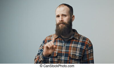 Discontent bearded hipster man denying waving finger...
