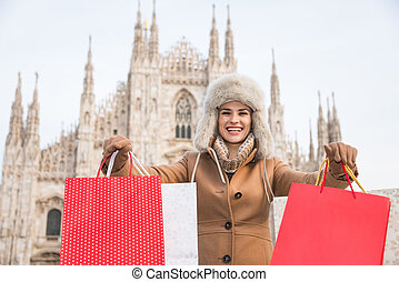 Smiling woman showing shopping bags in the front of Duomo