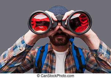Discovering new places. Confident young bearded man carrying backpack and looking through binoculars while standing against grey background