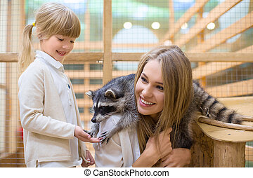 Discovery - Smiling family with raccoon in zoo
