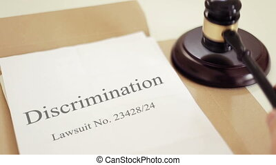 Discrimination lawsuit verdict folder with gavel placed on desk of judge in court