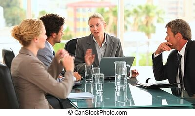 Discusion between four business people at a desk