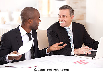 Discussing a project. Two cheerful business people in formalwear discussing something while one of them gesturing and smiling