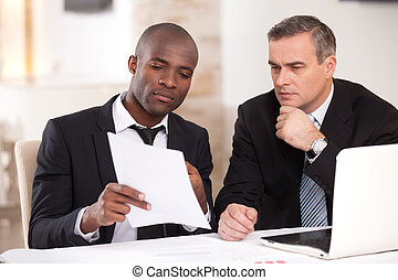 Discussing a project. Two confident business people in formalwear discussing something while one of them pointing a paper