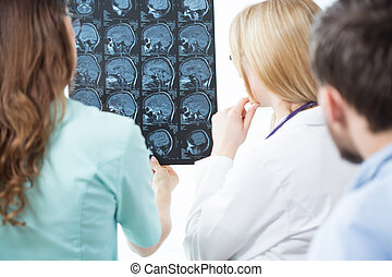 Discussing an MRI - Doctors in doctor's room discussing an...