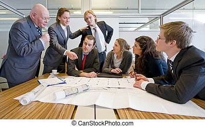 Discussing blue prints - A business team of architect and...