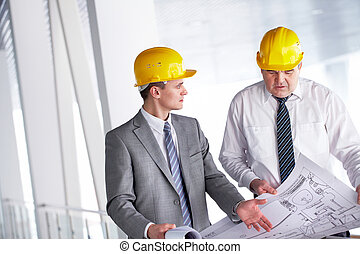 Discussing blueprint - Two architects discussing new project...