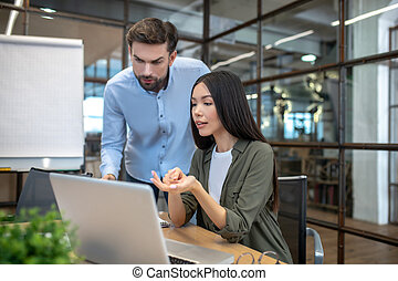 Two employees working in the office and looking interested