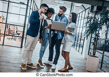 Discussing business together. Full length of young business people in smart casual wear concentrating on work while looking at the laptop