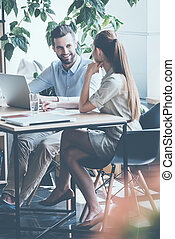 Discussing business. Two young business people in smart casual wear discussing something while sitting at the office desk together