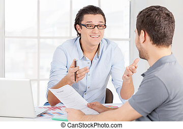 Discussing contract. Two cheerful business people in casual wear discussing something and gesturing while sitting at the table