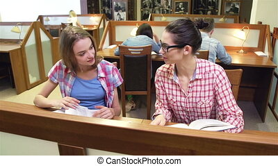 Discussing Items - Close up of two girls in the library...