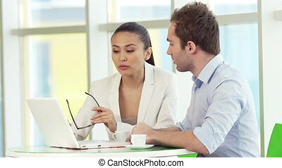 Discussing network - Two employees using laptop while...