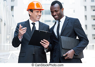 Discussing new building project. Cheerful contractor in hardhat gesturing and and smiling while standing together with African businessman