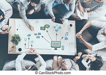 Discussing new strategy. Top view of business people discussing something while sitting around the desk together and pointing large paper with conceptual business icons drawn on it