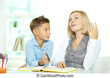 Portrait of pretty tutor sharing her idea of plot while discussing book with pupil