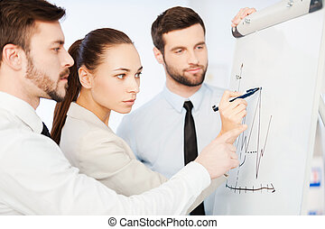 Discussing progress graph. Three confident business people discussing graph on the whiteboard while standing close to each other