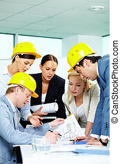 Discussing project - Group of architects looking at a ...