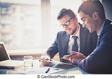 Discussing project - Image of two young businessmen using ...