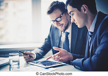 Discussing project - Image of two young businessmen using...