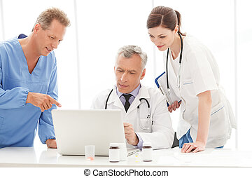 Discussing the report. Medical doctors team discussing...