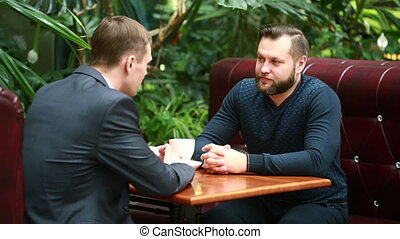discussion in a coffee shop by two businessmen