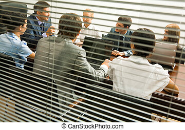 Discussion in office - View from behind venetian blind of...