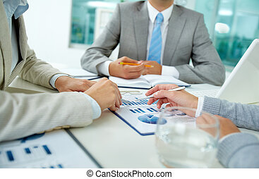 Discussion in team - Image of female hands with pens over...