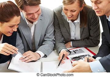 Discussion - Photo of business partners discussing document...