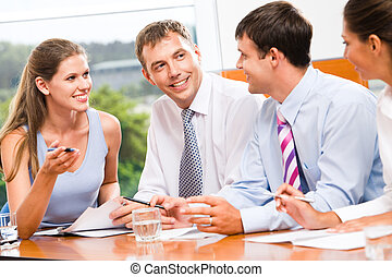Discussion - Portrait of several business people sitting in...