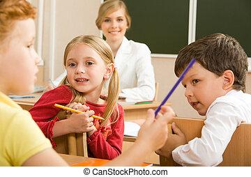 Discussion - Portrait of schoolchildren sitting in classroom...