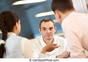 Discussion - Three businessmen sitting at table and ...
